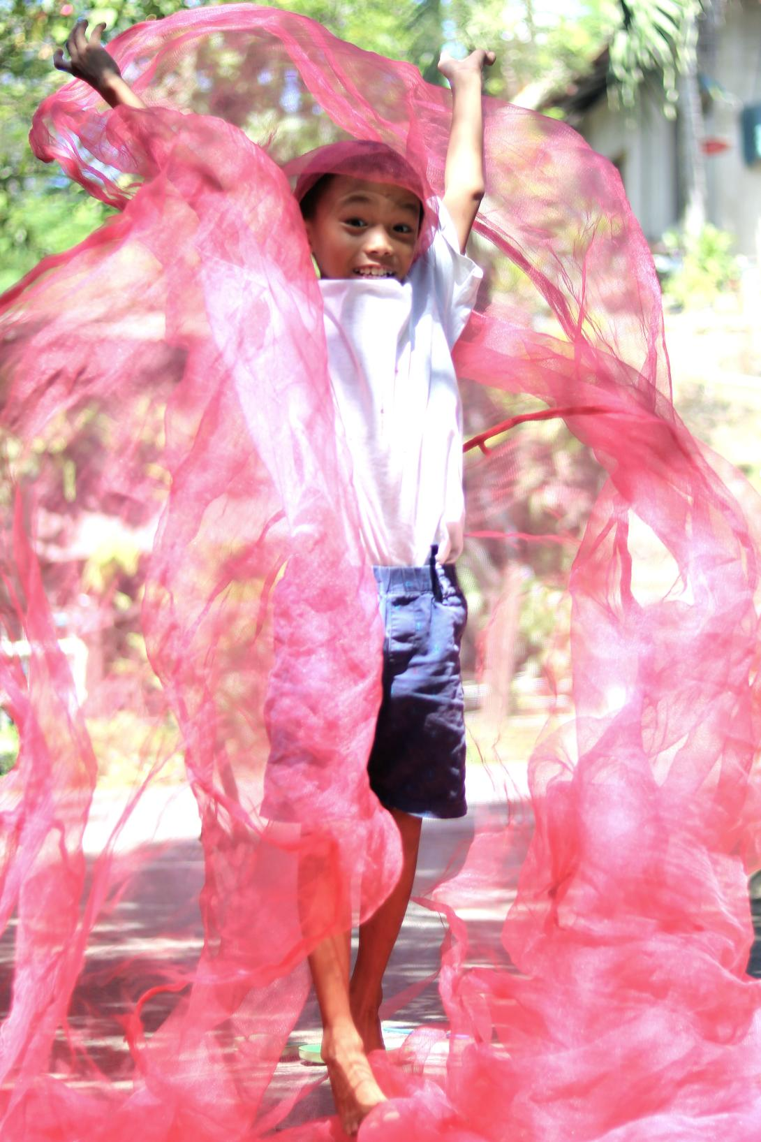 Local boy plays in a mosquito net in the Philippines.